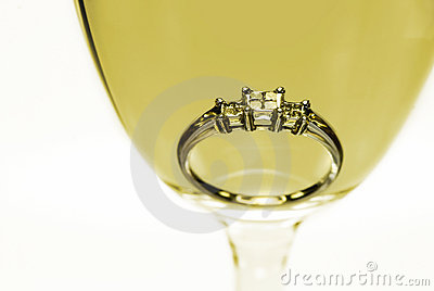 Diamond ring in a glass of white wine