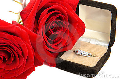 Diamond Ring Next to Two Red Roses