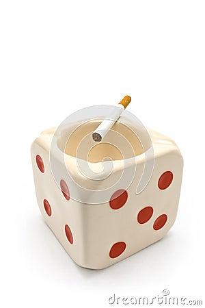 Dice shaped ashtray with burning cigarette