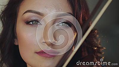Dicht portret van mooie vrouwelijke violist die de strijkstok op koord slingeren stock video