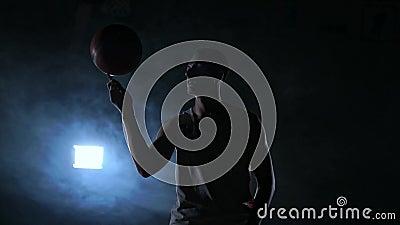 Dichte lengte van de spinnende bal van de basketbalspeler op zijn vinger, donkere nevelige ruimte met schijnwerper stock videobeelden