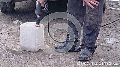 Die Arbeitskraft gießt Brennstoff in den Kanister und versehentlich in die Flecken stock footage