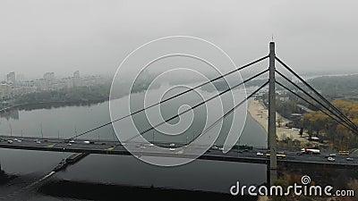 Die Betonbrücke mit dem Autoverkehr wird auf zwei Seiten der Metropole kombiniert Große graue Brücke mit Autos über den Fluss in  stock footage