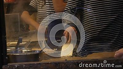 Die Chefköche bereiten Omeletts, Pfannkuchen, Nudeln und andere köstliche Gerichte in einem Fast-Food-Kiosk zu Seitenansicht von  stock video