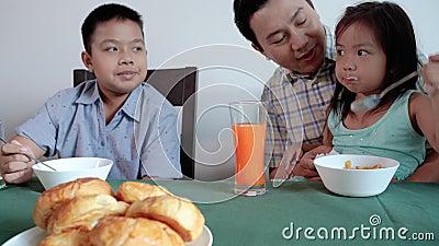 Die Familie gibt der Tochter zu schnappen Frühstück für sich selbst, lernen, sich selbst zu helfen stock footage