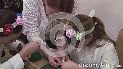 Die Frau, die zwei jugendlich Mädchen in der Blume unterrichtet, fassen ein, wie man Beadwork bei Tisch macht handmade kreation stock video footage