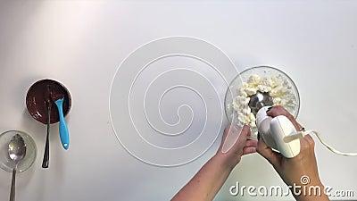 Die Frau mischt eine Mischmaschine in einem Behälter Hüttenkäse und Zucker mit geschmolzener Butter Bereitet die Füllung für glas stock footage
