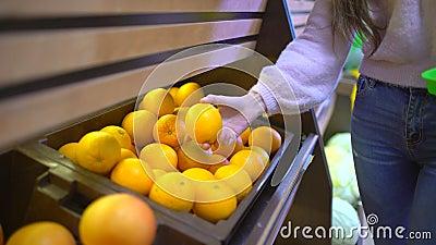 Die Frauenhand, die Zitronen hebt wählt im Supermarkt, Zitronen am Obst- und Gemüse Gang in einem Supermarkt auf stock video