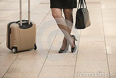 Die Geschäftsfrau, die mit Reise steht, bauscht sich auf Stadtbürgersteig