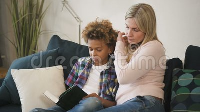 Die glückliche Familie liest zusammen die Geschichte aus einem Buch, das kleine Junge hält stock footage