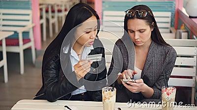 Die glücklichen Mädchen, die asiatisch und kaukasisch sind, leisten Online-Zahlung mit der Bankkarte, die im Internet-Shop zahlt, stock video footage