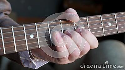 Die Hand des Mannes bewegt sich entlang des Gitarrenhalses Gitarre spielt Nahaufnahme stock footage