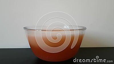 Die Hand einer Frau setzt eine Badebombe in eine Schüssel Wasser ein Das Wasser fängt an, Leuchtorange und Blutgeschwür zu drehen stock video