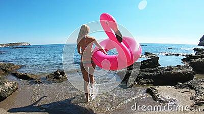 Die junge schlanke Frau genießt das Meer und die Sonne gehend in das Wasser mit einem rosa aufblasbaren Flamingo stock footage
