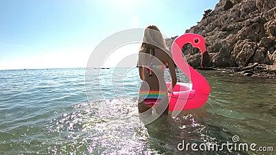 Die junge schlanke Frau genießt das Meer und die Sonne gehend in das Wasser mit einem rosa aufblasbaren Flamingo stock video footage