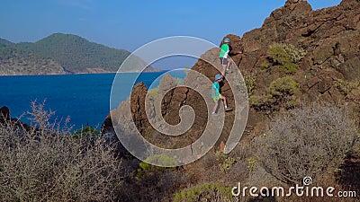 Die Jungen klettern auf den Felsen am Mittelmeer stock video footage
