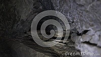 Die Strahlen der Laternen erhellen ein tiefes Loch in der Höhle stock footage