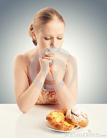 Diet concept. woman mouth sealed with duct tape with buns