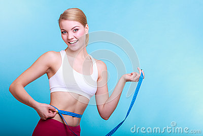 Diet. Fitness woman fit girl with measure tape measuring her waist Stock Photo