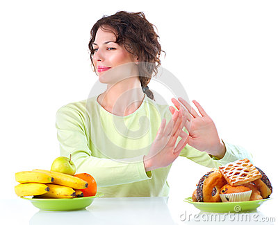 Diet. Woman choosing between Fruits and Sweets