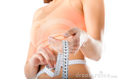 Diet - young woman is measuring her waist
