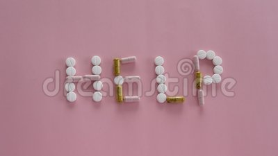Different medication pills in HELP word shape on pink background. Healthcare, medical concept. Addiction stock video footage