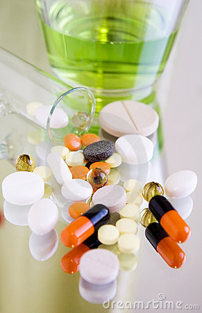 Different pills and medicines on a mirror surface
