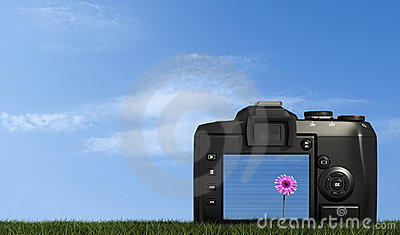 Digital camera on grass against blue sky