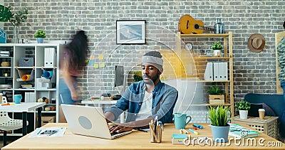 Diminuição do tempo de um cara afro-americano trabalhando com laptop no escritório video estoque
