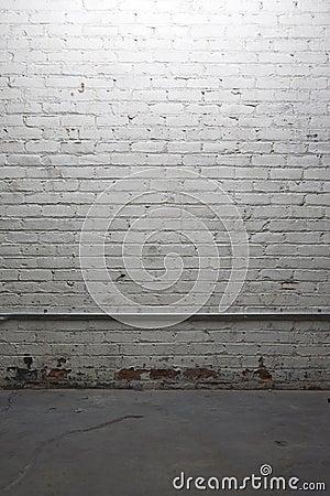 Dimly lit white brick wall