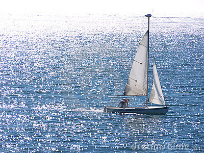 Dinghy sailing on silvery sea