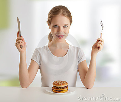 Dinner time.woman and knife, fork, hamburger
