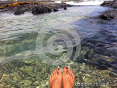 Dipping feet in tide pool in Hawaii