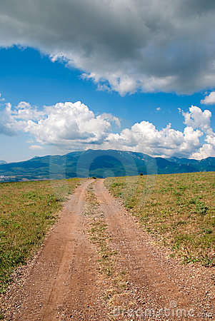 Direct dirt road, on horizon mountain hills