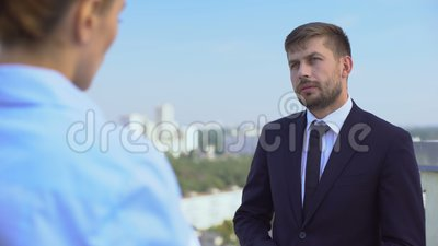 Directores masculinos y femeninos discutiendo sobre el trabajo en la terraza de la oficina, la carrera de socios almacen de video