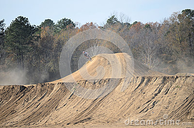 Dirt Bike Riding on Side of Large Hill Editorial Stock Photo