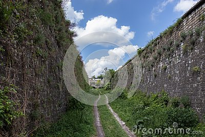 Dirt road between two stone ramparts Stock Photo