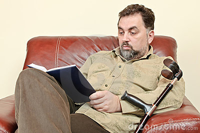 Disabled adult man reading a book