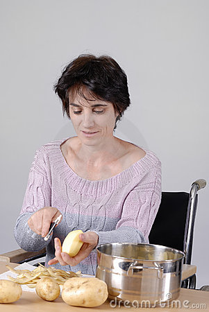 Disabled adult woman in wheelchair cooking dinner