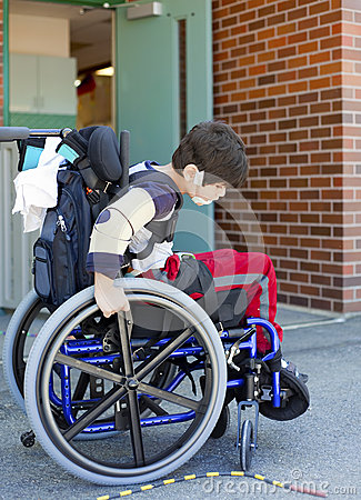 Disabled kindergartner in wheelchair on playground at recess