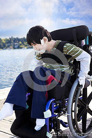 Disabled little boy in wheelchair out on pier by lake