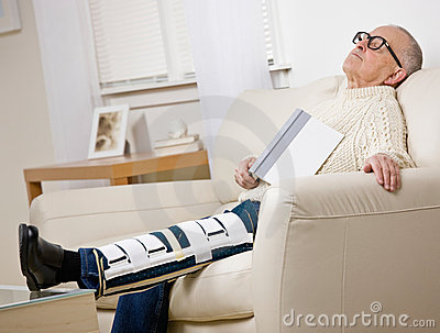 Disabled man with leg brace holding book