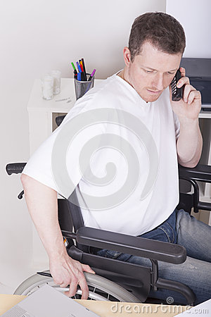 Disabled man in wheelchair in a home office