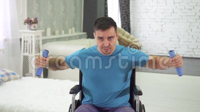 Disabled man in a wheelchair training with dumbbells at home slow