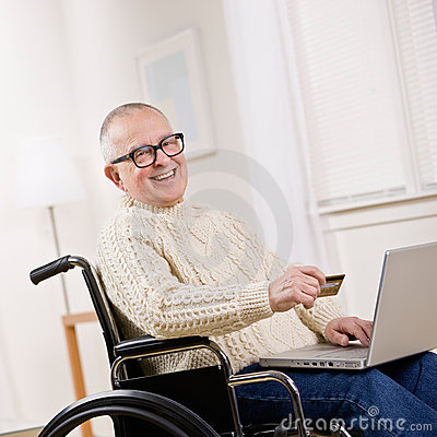 Disabled man in wheelchair using credit card