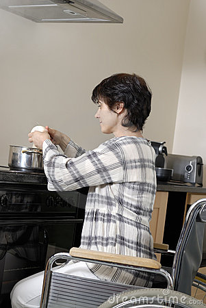 Disabled woman in wheelchair cooking dinner