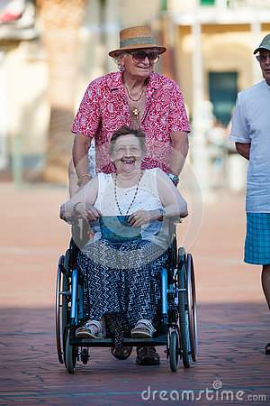 Disabled woman on a wheelchair. Love of an elderly couple. Editorial Stock Photo
