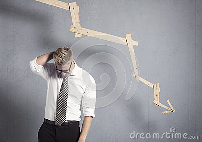 Disappointed businessman in front of graph pointing down.