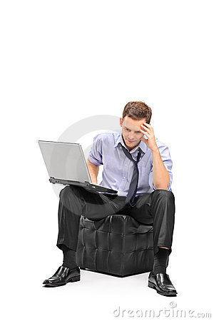 A disappointed businessman working on his laptop