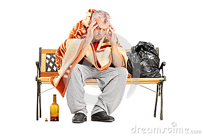 Disappointed homeless mature man sitting on a wooden bench